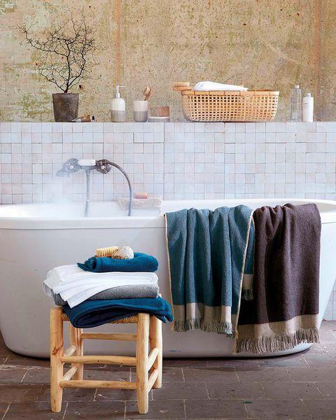 Baño con bañera exenta blanco y toallas de colores