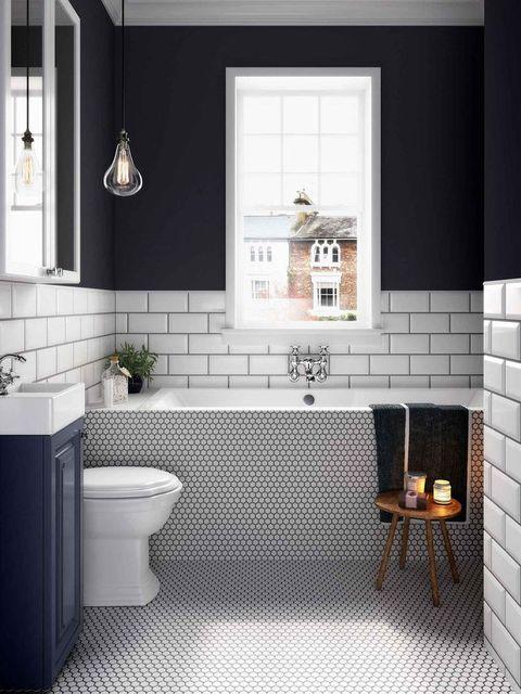Bañera revestida con un mosaico en tonos blancos y negros
