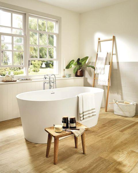 baño con bañera exenta moderna y suelo de madera alena, en surfex®