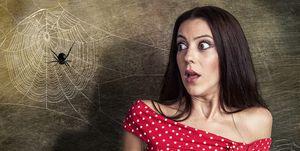 Vrouw kijkt bang naar spin in spinnenweb
