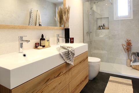 baño con ducha de obra y mueble suspendido bajo lavabo
