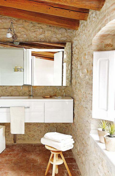 baño moderno con paredes de piedra y muebles blancos