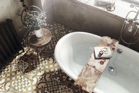 cuarto de baño con bañera exenta y suelo hidráulico