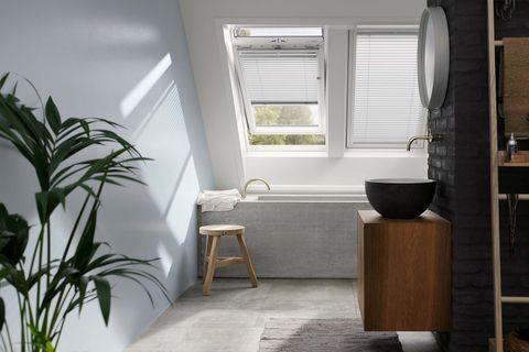 baño moderno abuhardillado con ventanas en el techo y cortinas venecianas