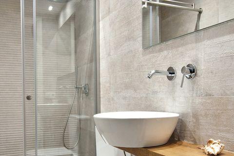 Baño moderno en blanco y gris con mampara de cristal