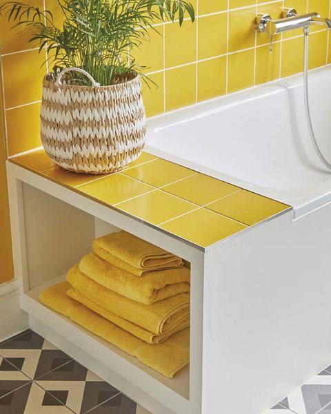 bañera con espacio de almacenaje para toallas azulejos amarillos