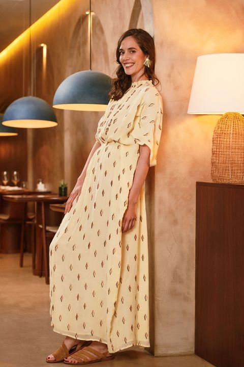 la actriz de la serie 'dos vidas', con vestido amarillo, sonríe a la cámara