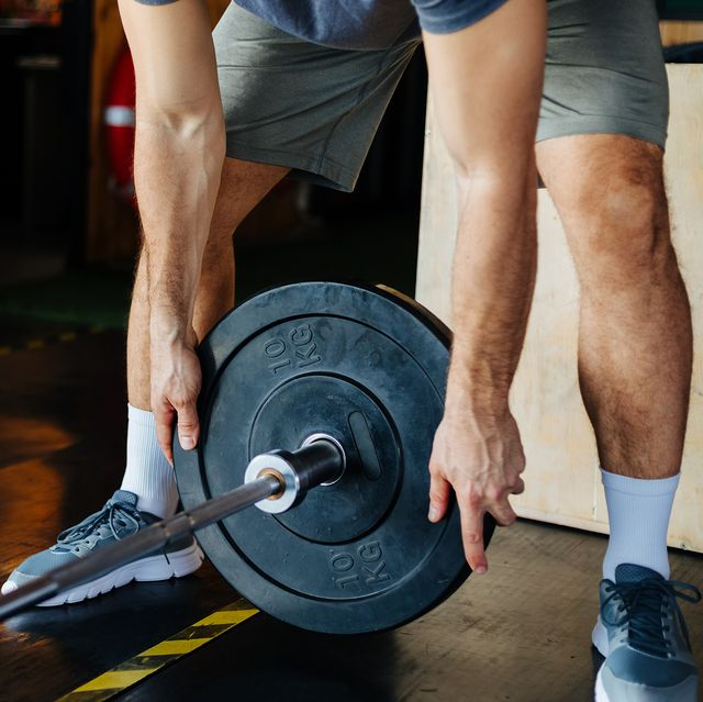 man putting weight on barbell bar