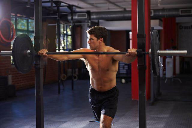 bare chested man in gym preparing to lift weights