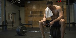 Bare chested man resting checking cell phone gym