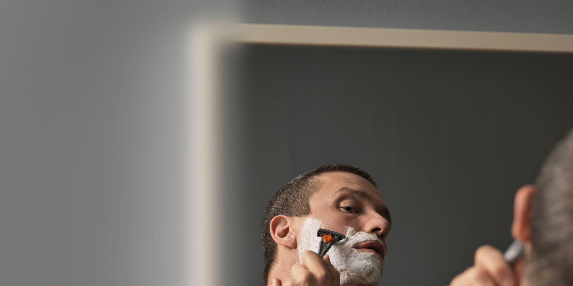 Bare chested man shaving