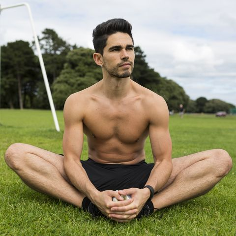 Barechested athlete sitting in grass