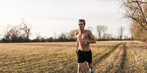 Barechested man running in rural landscape
