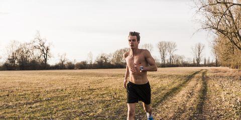 Barechested man running in rural landscape
