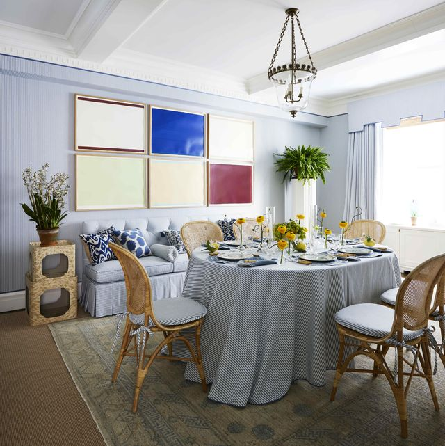 a blue and white dining room with a grid of modern art of the wall