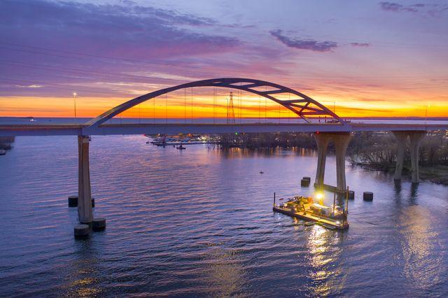 barge under scenic bridge at daybreak