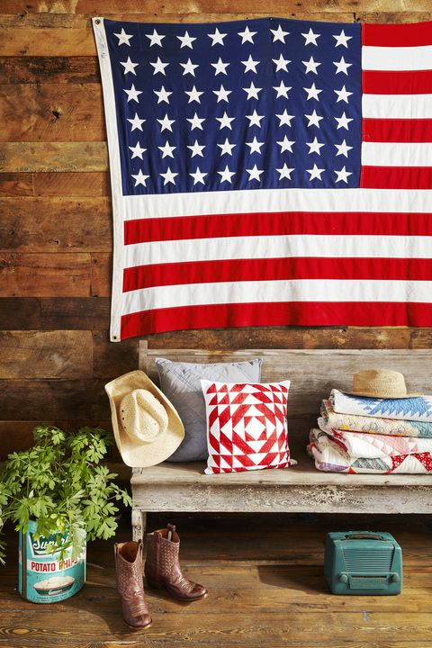 american flag hanging above a chippy bench in a barnwood covered entryway