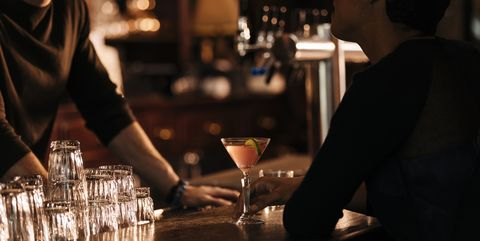 bartender talking to female customer at bar counter