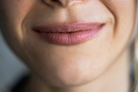 close up of smiling young woman lips with pink lipstick