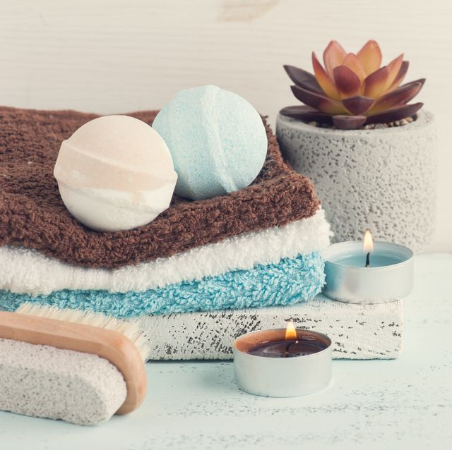 one white, one blue round bath bombs on top of stack of three washcloths, next to burning tea lights