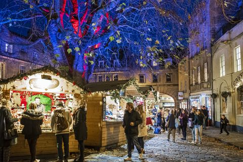 people at the christmas market set up in abbey green, in the old town of bath