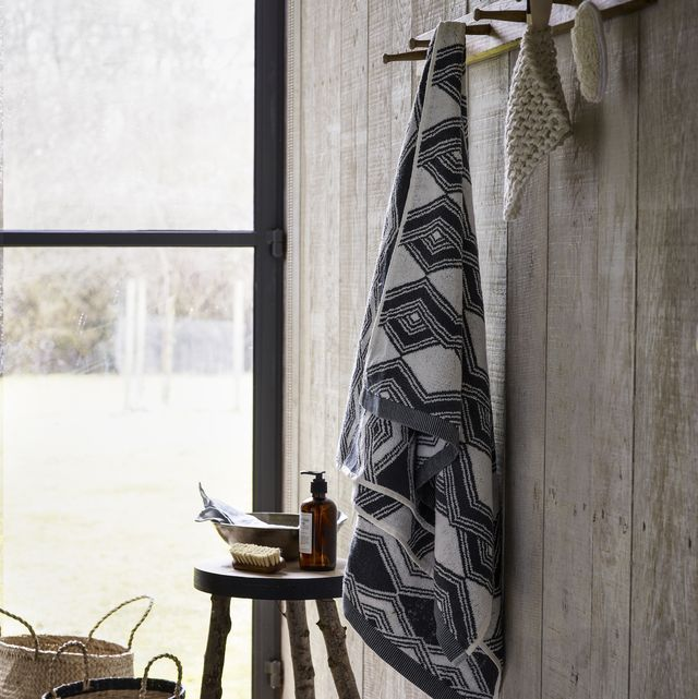 a rustic style country style bathroom, grey pattern towel and bath mits hang from a peg board fixed to a wooden wall, craft style stool, wicker baskets, corner of room, texture, neutral natural material, natural light,