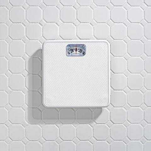 Bathroom scale on white tile floor.