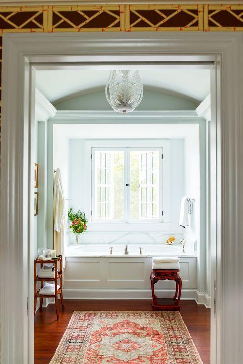 bathroom with bathtub and area rug