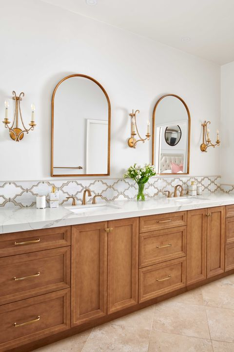 white bathroom, gold sconces, gold mirrors, wooden cabinets, marble countertops