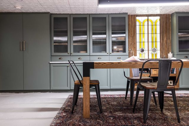 speakeasy, wooden table with black iron dining chairs, green storage cupboards