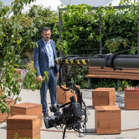 Adam Frost doing a piece to camera in a show garden at RHS Hampton Court flower show 2019. Hampton Court Palace, Surrey, UK