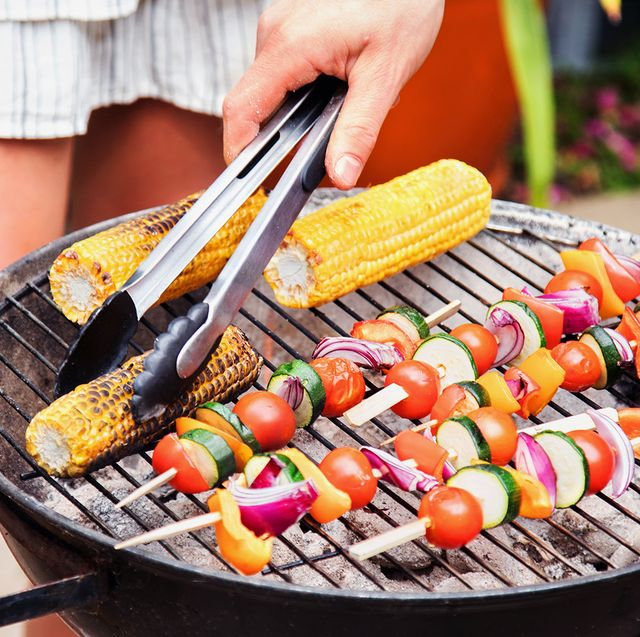 woman man and dog standing around charcoal bbq grill turning grilled corn and kebabs with tongs