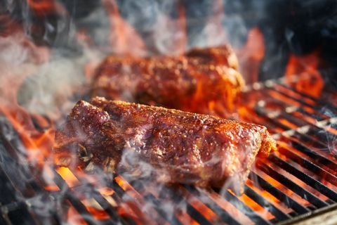 bbq pork ribs cooking on flaming grill