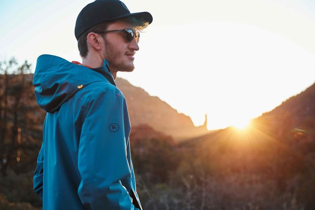 man wearing backcountry jacket looking into the distance as the sun sets