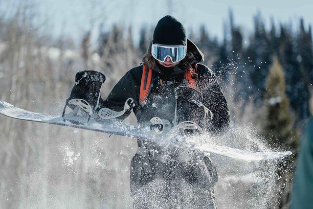 man wearing winter gear shaking snow off his snowboard