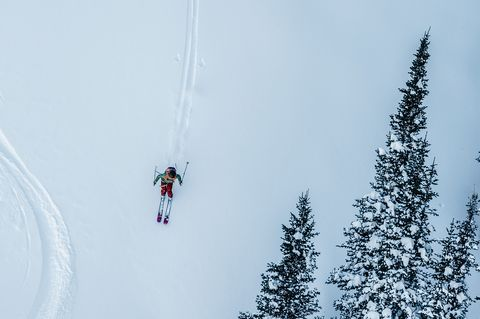 man wearing backcountry items skiing on a snowy hill