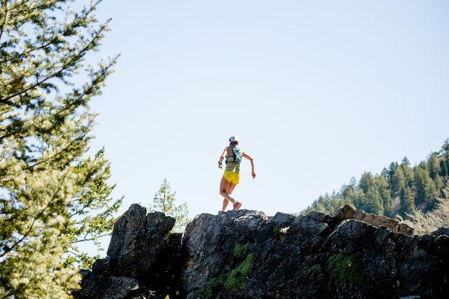 woman walking along cliff edge wearing backcountry gear