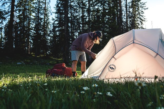 man setting up tent by forest