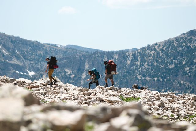 three people hiking on rocky terrain