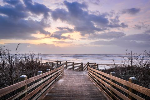 beach boardwalk at sunrise in port aransas, texas, usa