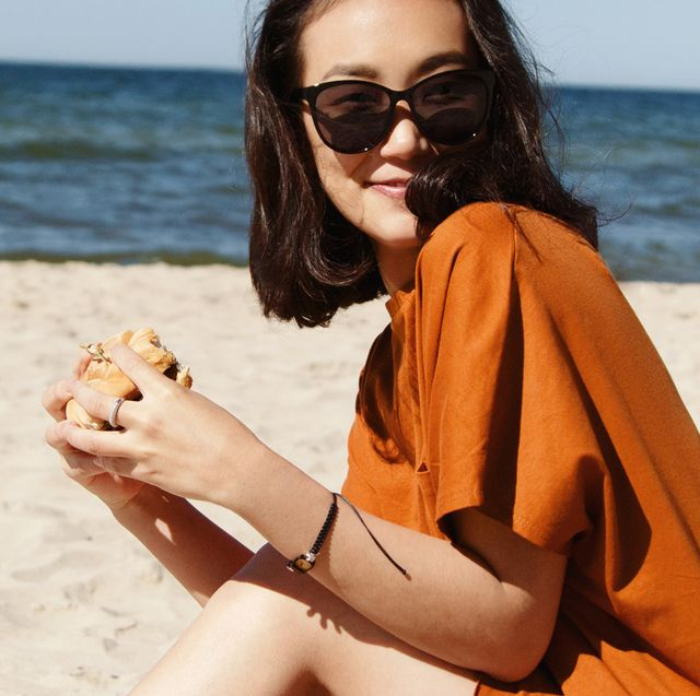 woman in sunglasses eating a burger on the beach