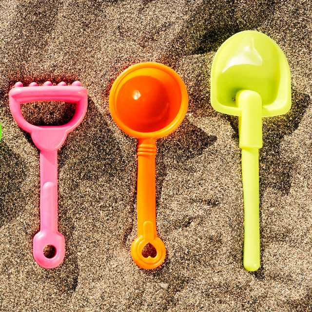 beach toys lined up in sand