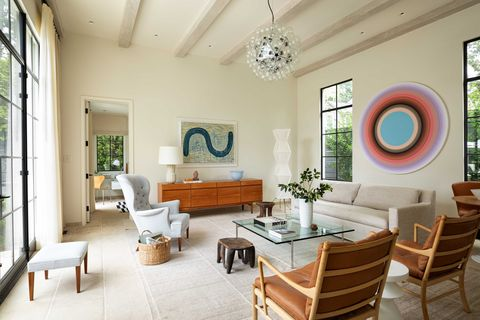 living room, cream painted walls, wooden ceiling beams, wooden side board, cream sofa couch, artwork