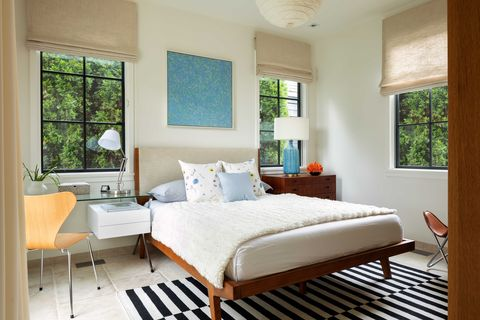 bedroom, white cream painted walls, tan curtains, black and white stripped rug, views of exterior trees