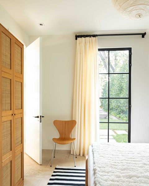 bedroom, black and white stripped rug, tiles, white linen, white throw rug, brown chair