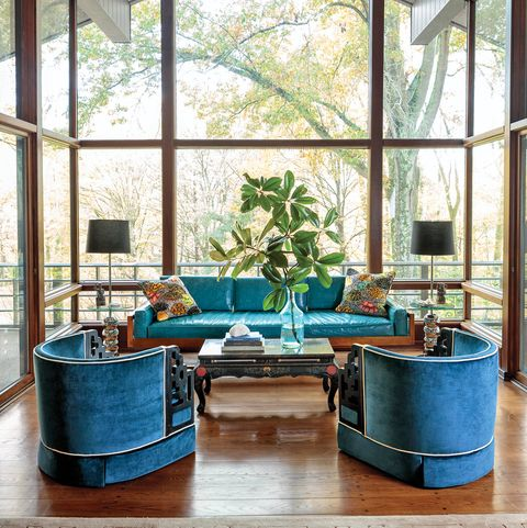 Glass-enclosed living room with high ceilings and blue furniture