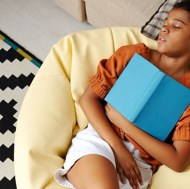 young girl sleeping on bean bag with book