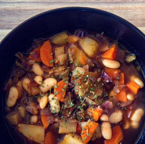 White beans soup with onion, carrot, potatoes and various vegetables in a black plate with a bit of parsley on top and spoon on the side.