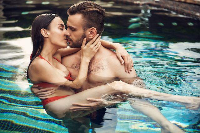 bearded man holding pretty black haired woman in red swimsuit