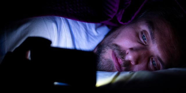 bearded young man is lying in bed under his blanket looking at phone